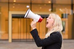恼怒的妇女抗议者叫喊入扩音机 免版税库存照片
