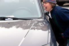 恼怒的妇女获得违规停车罚单 免版税库存照片