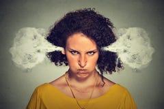 恼怒的妇女,从耳朵出来的吹的蒸汽 免版税库存照片