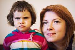 恼怒的孩子和微笑的母亲 库存照片