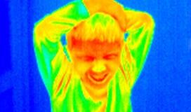 恼怒的孩子自计温度计 图库摄影