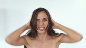 恼怒的少妇震动她的头发并且在白色背景前尖叫身分 股票录像