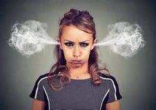恼怒的少妇,从耳朵出来的吹的蒸汽特写镜头画象  免版税图库摄影