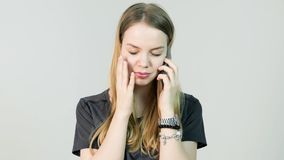 恼怒的少妇,啼声,与她的手机,美丽的女孩混淆,哀伤,紧张,翻倒,重音和认为 库存图片