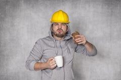 恼怒的工作者吃了一个三明治 免版税库存照片