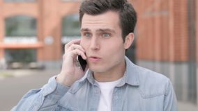 恼怒的年轻人谈话在电话