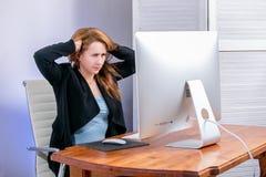 恼怒的年轻女实业家画象在办公室 她坐在桌上并且拿着她的头 星期一黑星期五或网络 n 图库摄影