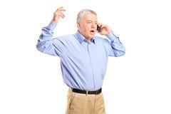 恼怒的成熟人谈话在电话 库存照片