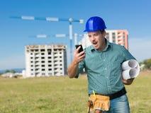 恼怒的承包商尖叫对电话 免版税库存图片