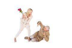 恼怒的有玫瑰色花束的妇女攻击的伙伴 库存照片