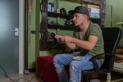 恼怒的游戏玩家演奏比赛和抽烟的香烟 库存照片