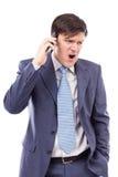 恼怒的生意人发表演讲关于移动电话和呼喊 库存图片