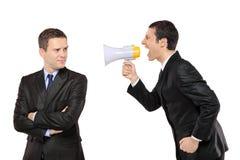 恼怒的生意人扩音机通过叫喊 免版税库存照片