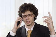 恼怒的生意人解释电话 库存照片