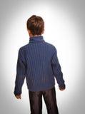 恼怒的男孩被转动握紧他的拳头的灰色愤懑孩子是 免版税库存图片