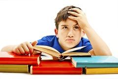 恼怒的男小学生有学习困难,查寻 免版税库存图片