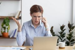 恼怒的疯狂的女实业家谈话在看膝上型计算机的电话 库存图片
