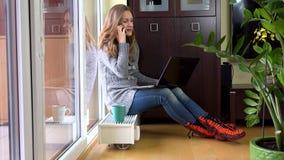 恼怒的疲乏的妇女在膝盖打与电话和膝上型计算机的企业电话 股票视频