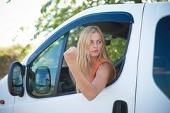 恼怒的白肤金发的女孩画象白色汽车陈列的 库存照片