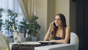 恼怒的美丽的妇女在餐馆告诉她的手机的男朋友,当单独等待他,然后离开时 股票录像