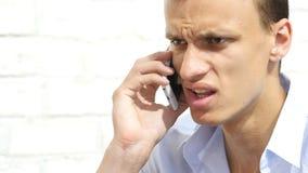 恼怒的翻倒人谈话在智能手机,谈话 免版税库存照片