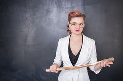 恼怒的老师用在黑板的木棍子 库存图片