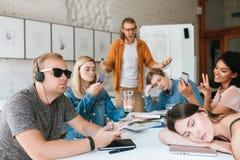 恼怒的老师站立近的委员会和尖叫在学生,因为他们aren ` t听他 编组学员 免版税库存图片