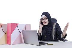恼怒的阿拉伯妇女谈话在手机 库存图片