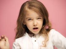恼怒的青少年的女孩画象桃红色演播室背景的 免版税库存照片