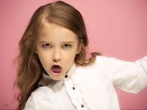 恼怒的青少年的女孩画象桃红色演播室背景的 免版税库存图片