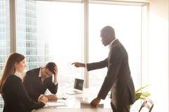 恼怒的非裔美国人的上司叫喊对白种人雇员, scol 免版税图库摄影