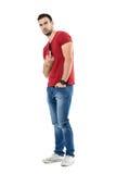 恼怒的年轻人佩带的显示淫秽中指的牛仔裤和红色T恤杉打手势 库存图片