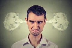 恼怒的年轻人,从耳朵出来的吹的蒸汽 免版税库存照片