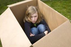 恼怒配件箱纸板女孩坐少年 库存照片