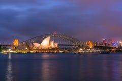 悉尼歌剧院和港口桥梁日落的澳大利亚看法  库存照片