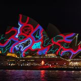 悉尼歌剧院在与样式在生动的轻的节日-在大厦的销售的上投射的晚上打开了 库存照片