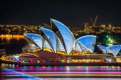 悉尼歌剧院在明亮的颜色打开了在晚上在生动的轻的节日 库存照片