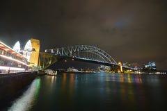 悉尼港桥,中心商务区&在晚上明亮地点燃了在左边的月神公园 库存照片