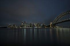 悉尼街市与歌剧院和港口桥梁在晚上, N 库存照片
