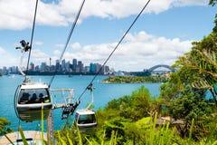 悉尼,澳大利亚- 2014年1月11日:在Taronga动物园的天空徒步旅行队缆车在有歌剧院和港口桥梁的悉尼 免版税图库摄影