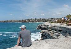 悉尼,澳大利亚- 2014年11月07日:坐在岩石边缘的未认出的人,接近海洋在悉尼,澳大利亚 免版税库存照片