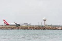 悉尼,澳大利亚- 2014年11月11日:悉尼国际机场与离开飞机 澳洲航空,空中客车A330-303, VH-QPC 免版税图库摄影