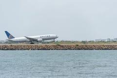 悉尼,澳大利亚- 2014年11月11日:悉尼国际机场与离开飞机 航空器N220UA,波音777-222,团结 免版税库存照片