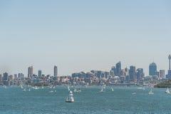 悉尼,澳大利亚- 2014年11月08日:悉尼都市风景用Westfield塔、企业摩天大楼和水与Yach 风景 库存照片