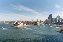 悉尼,澳大利亚- 2014年11月17日:有商业区和歌剧院的悉尼港口 都市风景 免版税库存图片