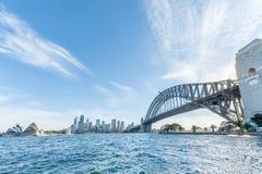 悉尼,澳大利亚- 2014年11月17日:有商业区和歌剧院的悉尼港桥 都市风景 阳光 免版税库存照片