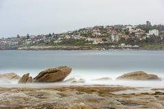 悉尼,澳大利亚- 2014年11月15日:长的曝光海滩照片用岩石和水 Nd过滤器 库存照片