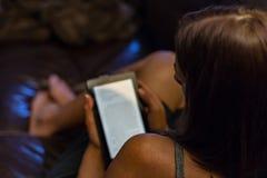 悠闲享用在她的电子设备的一位小姐一本书 库存图片