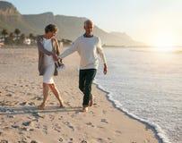 悠闲走在海滩的资深夫妇 库存照片