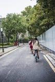 悠闲骑自行车的两少女沿古城墙壁 免版税库存照片